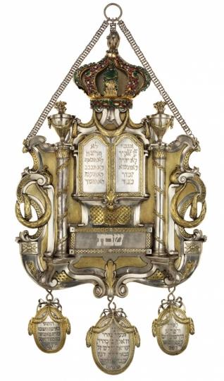 Štít na Tóru - Inv. č. ŽMP 046.075, stříbro, Praha, 1784, Richard Fleischmann, tepáno, cizelováno, lito, částečně zlaceno, osazeno smaragdy a rubíny, štít je součástí soupravy ozdob Tóry objednané do Pinkasovy synagogy jejím správcem Wolfem Zappertem v letech 1783-1784, vystaveno ve stálé expozici v zimní modlitebně Španělské synagogy