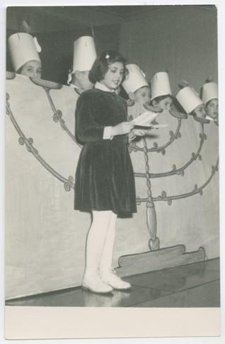 foto5.jpg - Chanuková oslava na Židovské náboženské obci v Praze v roce 1957. Na obrázku je Ivana Beranová, rozená v roce 1947. Pamětnice byla zapojena do hnutí Dětí Maiselovky. Kromě svých vzpomínek věnovala ŽMP v roce 2010 množství fotografií dokumentujících život židovské mládeže v druhé polovině dvacátého století.
